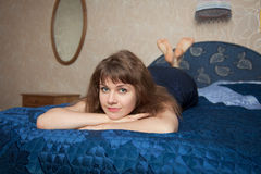 Beautiful girl in a dress lies on double bed Stock Photography
