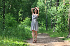 Beautiful girl in dress with long hair, walking on footpath Royalty Free Stock Photos