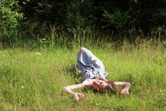Beautiful girl in dress lying on meadow in woods Stock Photos