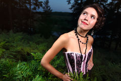 Beautiful girl in dress night forest. Hot young woman inside dark forest on dusk Royalty Free Stock Image