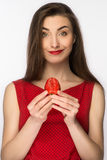 Beautiful girl in a dress with perfect smile eating red strawberry. Healthy food. Isolated on white. Stock Photos