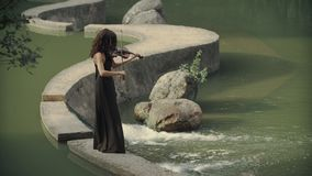 Beautiful girl in dress plays violin outdoors. Elegant violinist in forest stock video footage