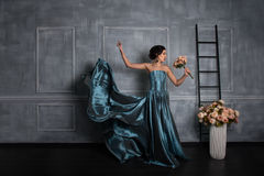 Beautiful girl in dress posing against a gray wall Royalty Free Stock Photo