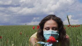 Beautiful girl in protective mask and gloves on wheat green field with red poppies sniffs a flower. Coronavirus COVID-19 epidemic