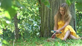 Beautiful girl in dress reading book sitting under tree take books and hat and walk away. 4K stock footage