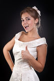 Beautiful girl in dress shows OK in the studio Royalty Free Stock Photos