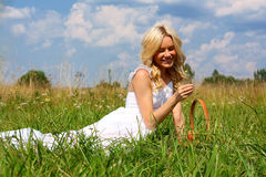 Beautiful girl in dress. Beautiful girl sitting on the green grass with a basket of fruit and smiling royalty free stock images
