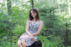 Beautiful girl in dress sitting on stump in forest Stock Image