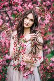 Beautiful girl in a dress stands near the tree blossoms with pink flowers, holding by the hand a sprig, looks up with a smile stock images