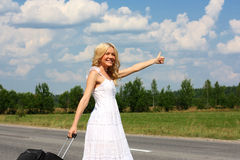 Beautiful girl in dress. Beautiful girl in a dress stands with a suitcase on daoroge royalty free stock images