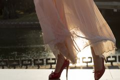 Beautiful girl in dress on sunset. legs in red shoes on the nature background stock photo