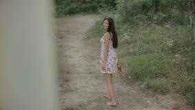 Beautiful girl in the dress walking along a path stock video