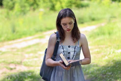 Beautiful girl in dress walking on glade reading book Royalty Free Stock Photo