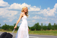 Beautiful girl in dress. Beautiful woman traveling with a suitcase royalty free stock photography