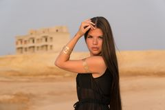 A beautiful girl dressed in Arabic style. In the background, the desert and the building.  Royalty Free Stock Photos