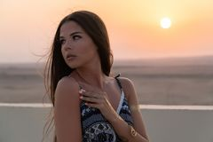 A beautiful girl dressed in Arabic style, standing on the roof at sunset. In the background, the desert and the sun.  Royalty Free Stock Image