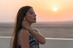 A beautiful girl dressed in Arabic style, standing on the roof at sunset. In the background, the desert and the sun.  Royalty Free Stock Photo