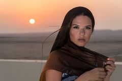 A beautiful girl dressed in Arabic style, standing on the roof at sunset. In the background, the desert and the sun.  Stock Photography