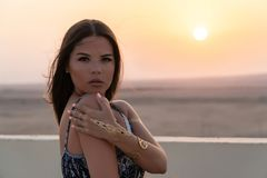 A beautiful girl dressed in Arabic style, standing on the roof at sunset. In the background, the desert and the sun.  Stock Images