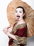 Beautiful girl dressed as a geisha girl holding a Chinese umbrella. Geisha makeup and hair dressed in a kimono. The. Concept of traditional Japanese values Stock Photography