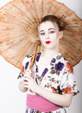 Beautiful girl dressed as a geisha girl holding a Chinese umbrella. Geisha makeup and hair dressed in a kimono. The. Concept of traditional Japanese values Stock Photo