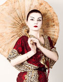 Beautiful girl dressed as a geisha girl holding a Chinese umbrella. Geisha makeup and hair dressed in a kimono. The. Concept of traditional Japanese values Royalty Free Stock Photography
