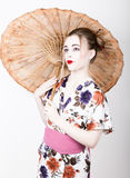 Beautiful girl dressed as a geisha girl holding a Chinese umbrella. Geisha makeup and hair dressed in a kimono. The Royalty Free Stock Photography