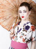 Beautiful girl dressed as a geisha girl holding a Chinese umbrella. Geisha makeup and hair dressed in a kimono. The Stock Photography