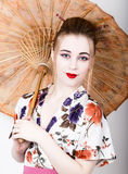 Beautiful girl dressed as a geisha girl holding a Chinese umbrella. Geisha makeup and hair dressed in a kimono. The Stock Images
