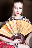 Beautiful girl dressed as a geisha, she holds a chinese fan. Geisha makeup and hair dressed in a kimono. The concept of Royalty Free Stock Photography