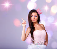 Beautiful girl dressed as a princess shows your text. Girl in a short dress and crown Royalty Free Stock Photography