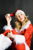 Beautiful Girl Dressed As Santa. Sexy beautiful blond girl dressed as Santa isolated against black background Royalty Free Stock Image