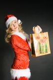 Beautiful Girl Dressed As Santa. Sexy beautiful blond girl dressed as Santa isolated against black background Stock Image