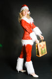 Beautiful Girl Dressed As Santa. Sexy beautiful blond girl dressed as Santa on black background Royalty Free Stock Photos