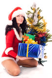 Beautiful girl dressed as santa. Beautiful brunette girl dressed as Santa puts presents under the Christmas tree Stock Photos