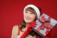Beautiful girl dressed as Santa holds a gift. Stock Photo