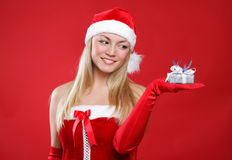 Beautiful girl dressed as Santa holds a gift. Stock Images