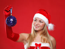 Beautiful girl dressed as Santa holds a gift. Royalty Free Stock Image