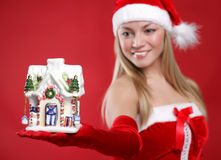 Beautiful girl dressed as Santa holds a gift. Royalty Free Stock Photos