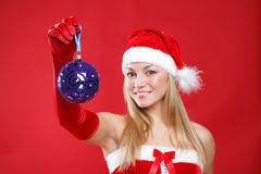 Beautiful girl dressed as Santa holds a gift. Royalty Free Stock Images