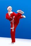 Beautiful girl dressed as Santa makes a karate kick left foot Royalty Free Stock Photo