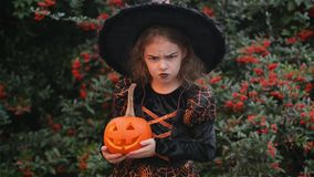 Beautiful girl dressed as a witch with a pumpkin-halloween with a burning candle, child screaming at the camera, Against stock video footage