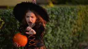 Beautiful girl dressed as a witch with a pumpkin-halloween with a burning candle, child screaming at the camera, outdoor stock video footage