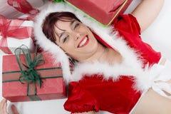 Beautiful girl dressed like Santa with Christmas presents Stock Photos