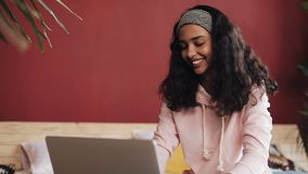 Beautiful girl dressed in pink pajamas using laptop computer sitting in bed at home. Young woman is smiling and chatting stock footage