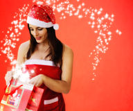 Beautiful girl dressed santa claus opens a  gift Stock Photo