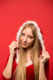 Beautiful girl dressed in santa claus over a red background Stock Images