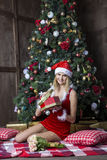 Beautiful girl dressed in santa suit near christmas tree Stock Photography