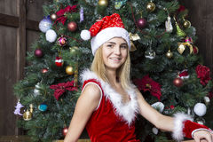 Beautiful girl dressed in santa suit near christmas tree Stock Photo
