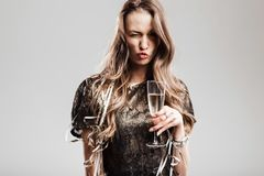 Beautiful girl dressed in stylish elegant black dress holds glass of champagne grimacing on a white background royalty free stock images